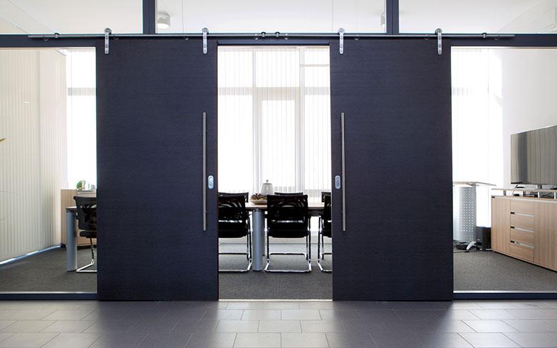 Optik im Loft-Stil: Ein markantes Merkmal dieser zweiflügeligen Schiebetür sind die offenen Beschläge im Industrie-Design.
